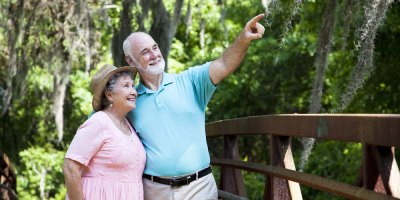 Senior couple walking on bridge, pointing at something