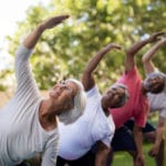 Senior people looking up while exercising with arms raised at park