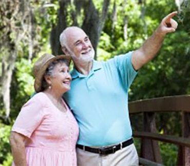 Elderly couple on walk pointing at something